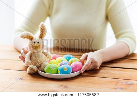 easter, holidays, tradition and people concept - close up of woman hands with colored easter eggs on plate and bunny