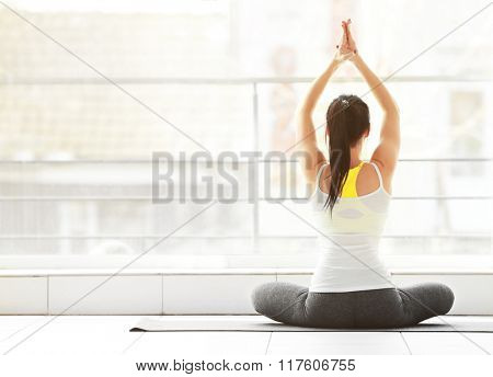 Health concept. Young attractive woman does yoga exercise in the gym  against window