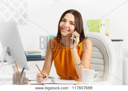A beautiful successful woman talking on phone at the modern office
