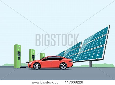 Electric Car Charging At The Charging Station In Front Of The Solar Panels