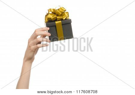 The Theme Of Celebrations And Gifts: Hand Holding A Gift Wrapped In A Black Box With Gold Ribbon And