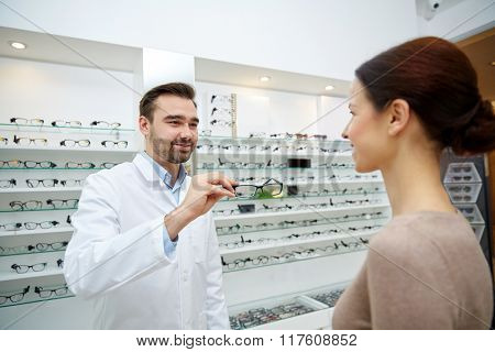 health care, people, eyesight and vision concept - optician giving glasses to woman at optics store