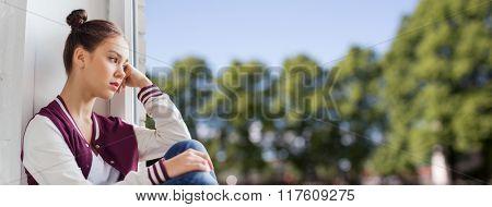 people, emotion and teens concept - sad unhappy pretty teenage girl sitting on windowsill over summer background