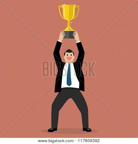 Businessman Holding Up A Winning Trophy