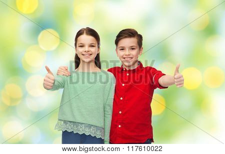 childhood, fashion, gesture and people concept - happy smiling boy and girl hugging and showing thumbs up over green lights background