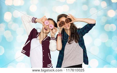 people, friends, teens and friendship concept - happy smiling pretty teenage girls with donuts making faces and having fun over blue holidays lights background