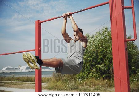 fitness, sport, exercising, training and lifestyle concept - young man doing abdominal exercise on horizontal bar in summer park