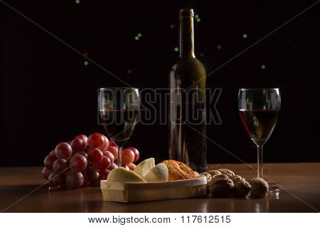Composition with wine, cheese, nuts and grape on wooden table, on black background