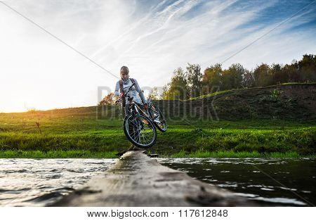 Lady with bicycle crossing the river