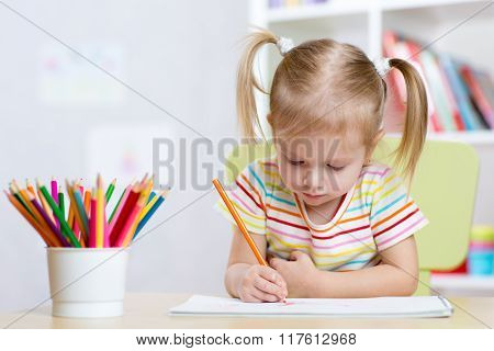 Child girl drawing with colorful pencils in nursery