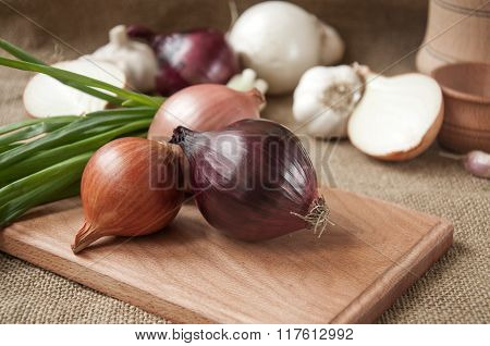 Various Onions On A Board On A Background Sacking, Burlap