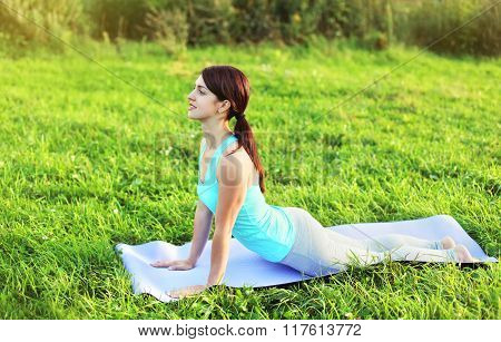 Woman Doing Yoga Exercises On Grass In Summer Park