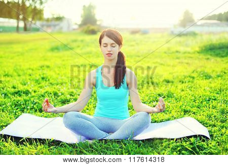 Yoga Woman Meditates On Grass Pose Lotus In Sunny Day
