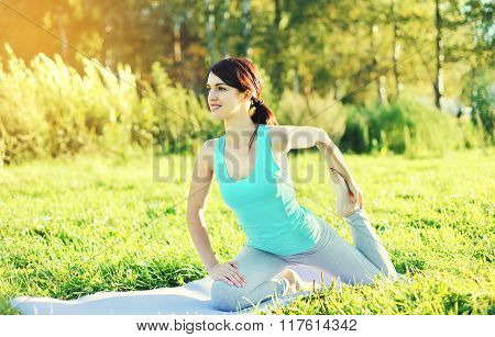 Young Woman Doing Yoga Exercises On Grass In Summer Sunny Day