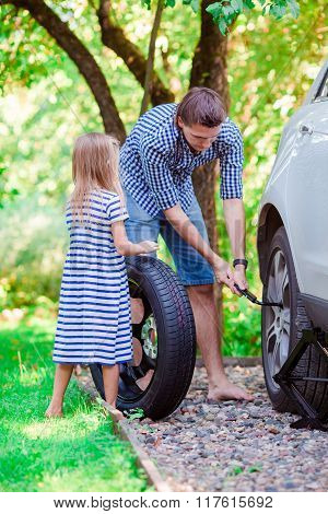Adorable little girl helping father to change a car wheel outdoors on beautiful summer day