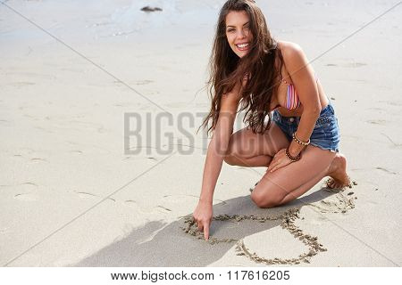 Beautiful young woman makeing a heart in sand