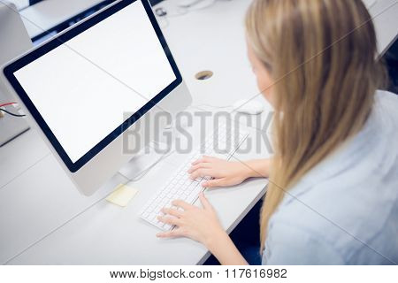 Rear view of student using computer at university