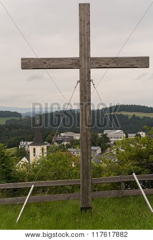 Large Wooden Cross In Front Of A Rural Community