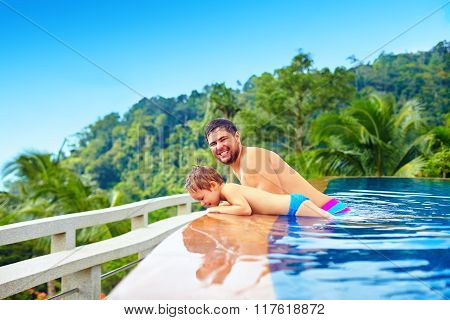 Happy Father And Son Relaxing In Infinity Pool On Tropical Island