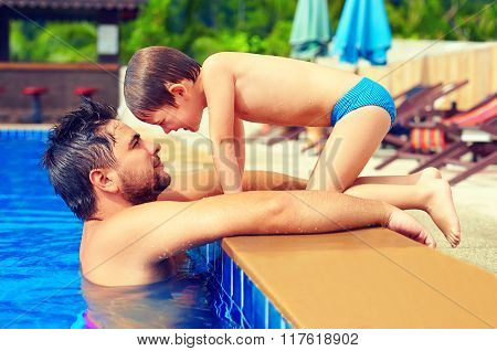 Happy Father And Son Enjoy Summer Vacation In Pool