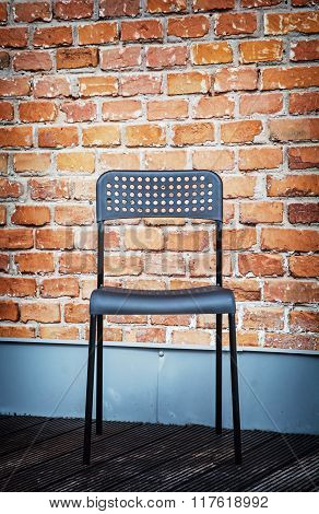 Metal Chair In Front Of The Brick Wall