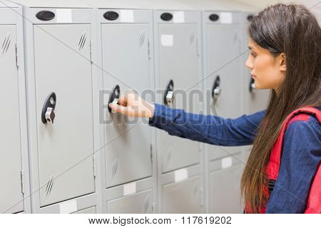 Unsmiling student opening her locker at university