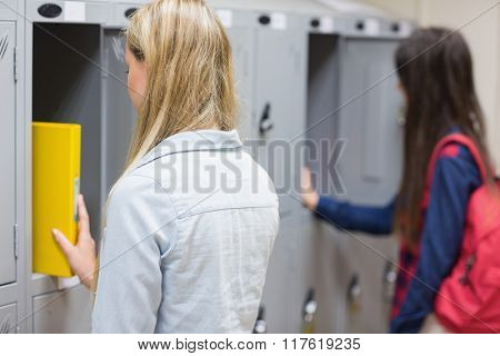 Smiling students using locker at university