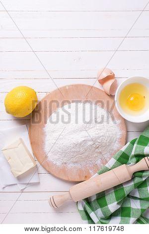 Ingredients For Dough - Flour, Egg, Butter, Lemon On White Wooden Background.
