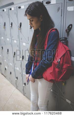 Sad student leaning on locker at university