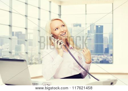 business, communication, people and technology concept - smiling businesswoman or secretary with laptop computer calling on telephone over office room with city view window background