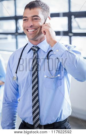 Happy doctor on the phone in the hospital