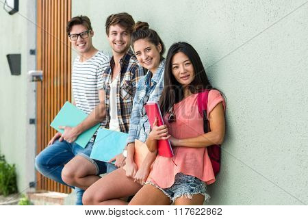 Hip friends leaning against wall and holding notebooks on the street