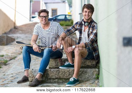 Hip men sitting on steps and looking at the camera in the city