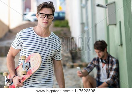 Hip man holding skateboard looking at the camera