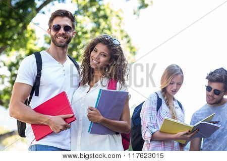 Hip friends holding notebooks and looking at the camera on the street