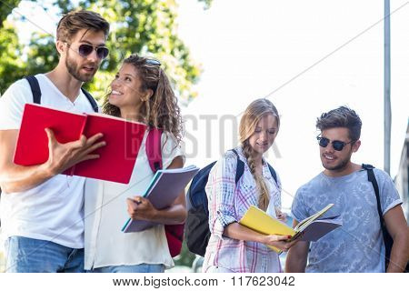 Hip friends reading notes on notebooks outdoors