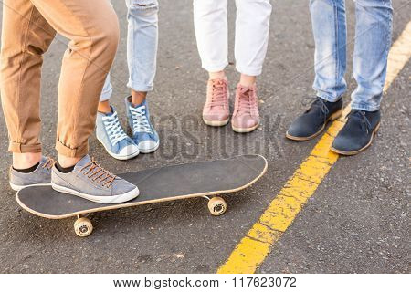 Lower section of hip friends and skateboard on the street
