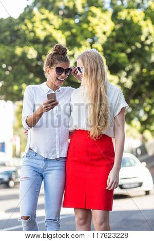 Hip woman looking at smartphone in the streets