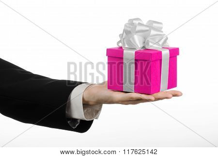The Theme Of Celebrations And Gifts: Hand Holding A Gift Wrapped In Pink Box With White Ribbon And B