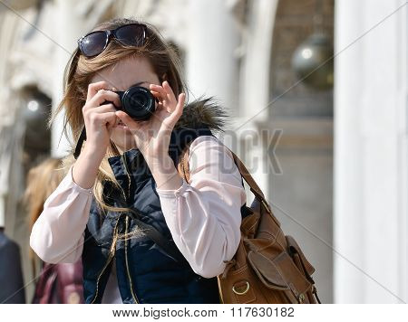 Venice, Italy - December 05, 2016: Young woman photographer taking pictures in San Marco square