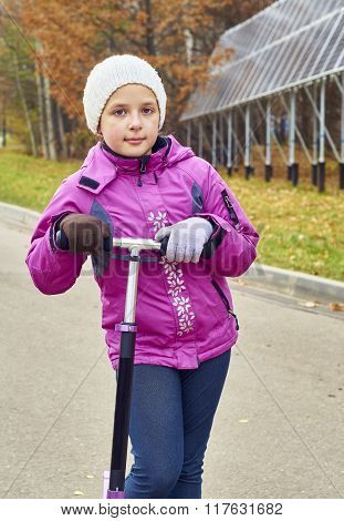 Happy schoolgirl posing with a scooter in the park
