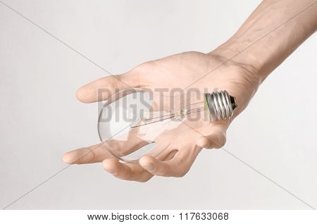 Energy Consumption And Energy Saving Topic: Human Hand Holding A Light Bulb On A White Background In