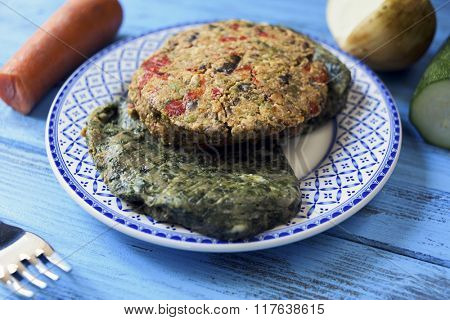 closeup of some different veggie burgers in a ceramic plate, on a rustic blue wooden table