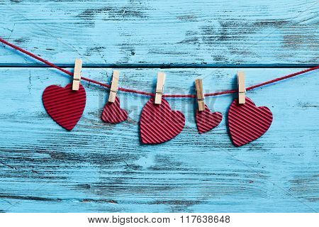 some hearts, made with red corrugated paperboard, hung with clothespins in a clothes line, against a blue rustic wooden background