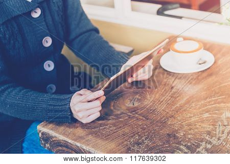 Woman Using Tablet And Depth Of Field In Coffee Shop With Vintage Tone.