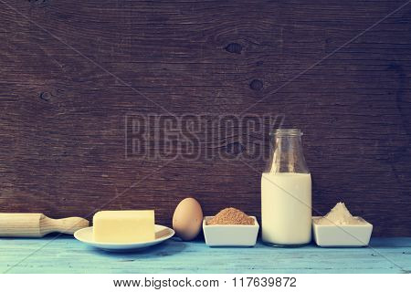 some ingredients for preparing cookies or a cake, such as milk, eggs, flour, butter and brown sugar on a blue rustic wooden surface, with a retro effect