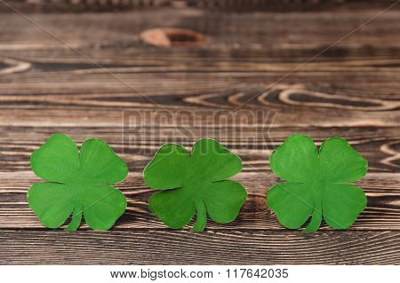 Four leaf clovers on wooden background