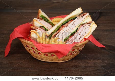 basket of chicken club sandwich and fries