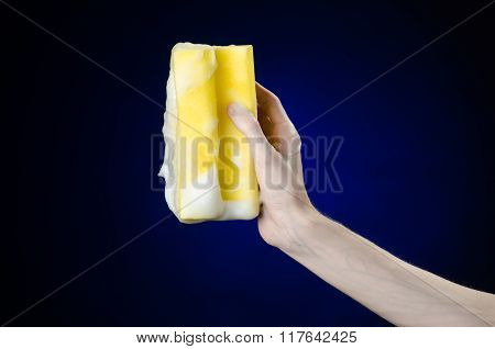 Cleaning The House And Sanitation Topic: Hand Holding A Yellow Sponge Wet With Foam On A Dark Blue B