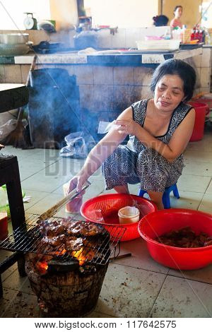 Woman is cooking meat on the fire at the vietnamese style food court
